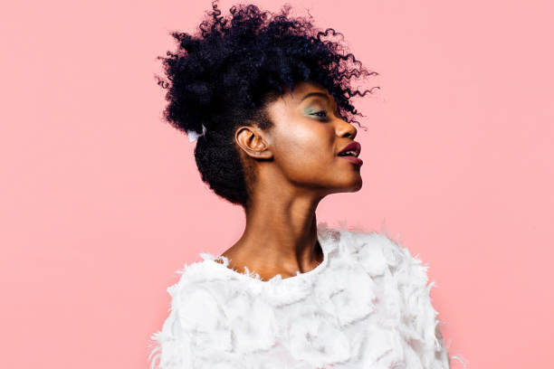 profile portrait of a beautiful young woman with curly black hair, isolated on pink background - carlos david stock pictures, royalty-free photos & images