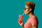istock Profile portrait of a cool young  woman in pink holding a drinking cup and paper straw 1255751395