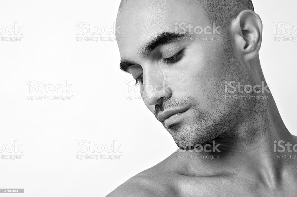 Profile portrait of a handsome bald man looking down. stock photo