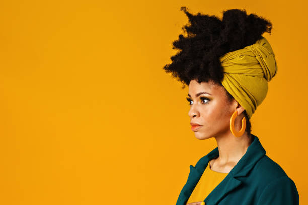 profile portrait of a serious young woman with big yellow earrings and afro hair wrapped with scarf - carlos david stock pictures, royalty-free photos & images