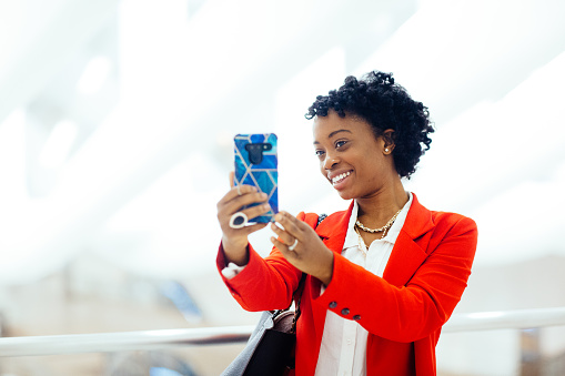 Profile portrait of a woman in red business jacket holding and using her cell phone