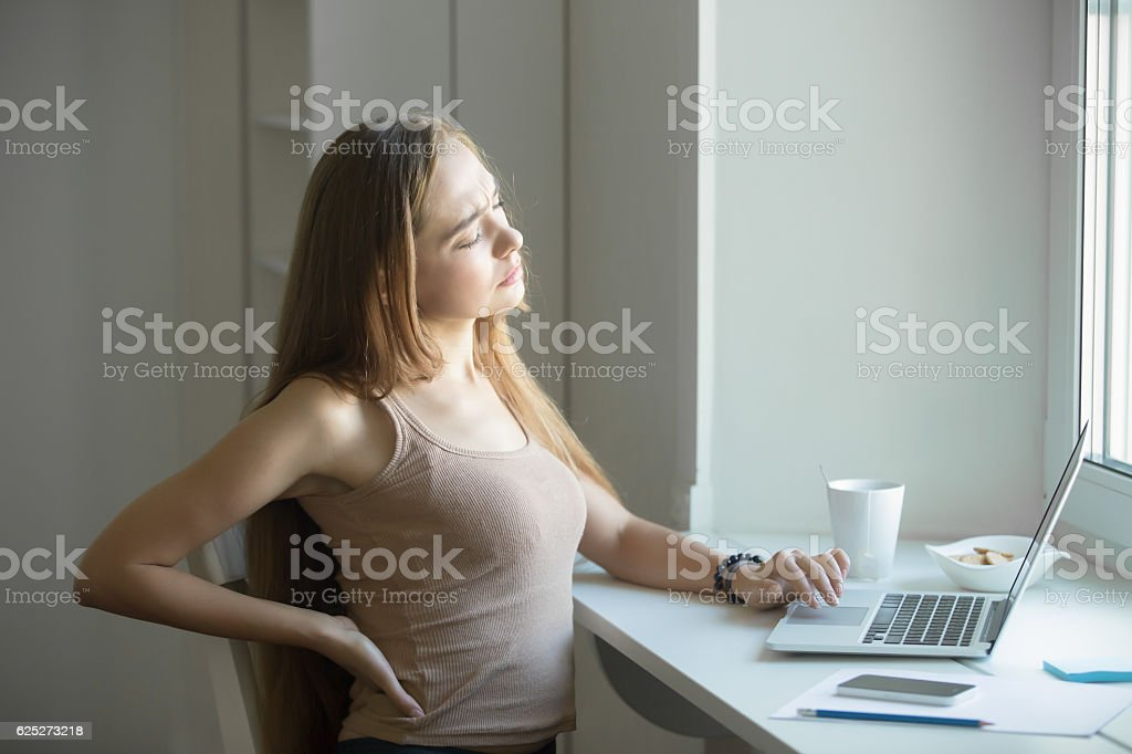 Profile portrait of a young woman, stretching working at laptop stock photo