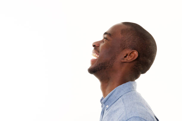 Profilportrait des hübschen jungen schwarzen Mannes, der vor isoliertem weißen Hintergrund lacht – Foto