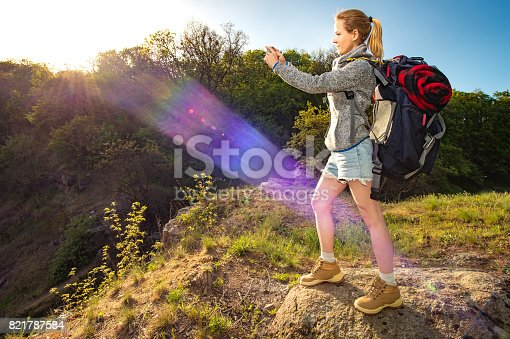 629376126istockphoto Profile portrait of happy sporty woman traveler, Female model doing landscape photography with smartphone at morning sun beam, Healthy active concept 821787584