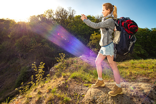 629376126 istock photo Profile portrait of happy sporty woman traveler, Female model doing landscape photography with smartphone at morning sun beam, Healthy active concept 821787584