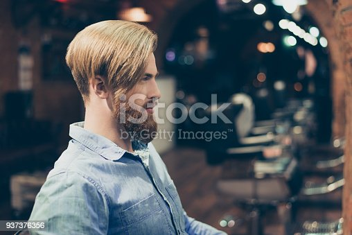 698023272 istock photo Profile portrait of harsh stylish red bearded man in a barber shop. His hairstyle is spectacular and so trendy! 937376356