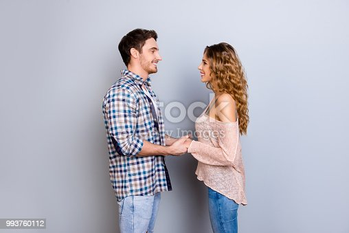 Profile portrait of lovely joyful couple holding hands looking at each other enjoying time together isolated on grey background