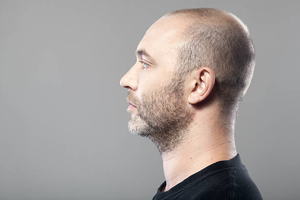 profile portrait of man isolated on gray background with copyspace profile portrait of man isolated on gray background with copyspace shaved head stock pictures, royalty-free photos & images