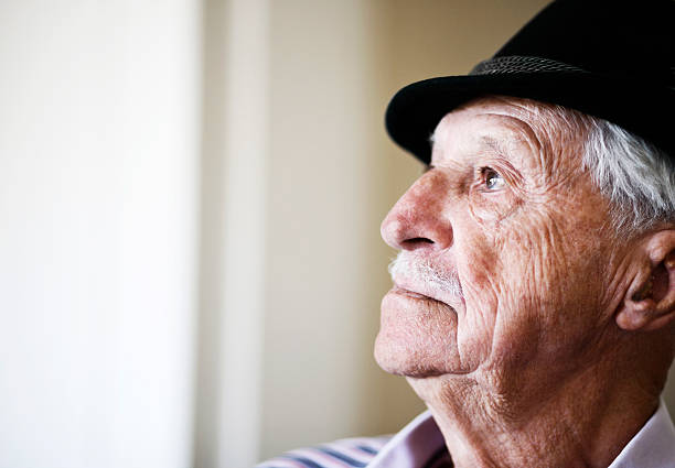 Profile portrait of serious 80 year old man in hat stock photo