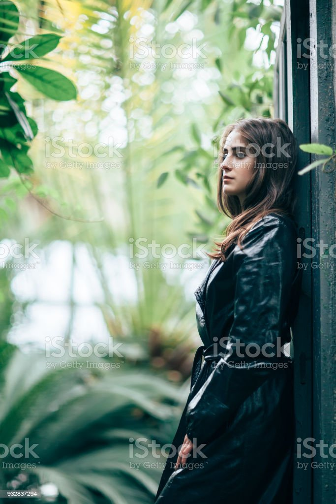 Profile portrait of young fashion woman in black jacket leaning back door jamb stock photo