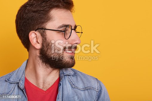 542972720 istock photo Profile portrait on turned head and well trimmed beard of handsopme man with glasses, wearing red shirt and stylish denim jacket, guy looking aside, copy space for advertisment or promotion text. 1174090871