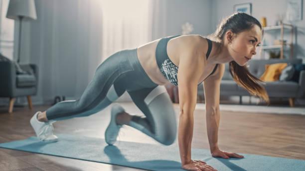 ProfilAufnahme einer schönen selbstbewussten starken Fitness-Frau in einem grauen Athletik-Outfit tun Bergsteiger Übungen in ihrem hellen und geräumigen Apartment mit gemütlichen minimalistischen Interieur. – Foto