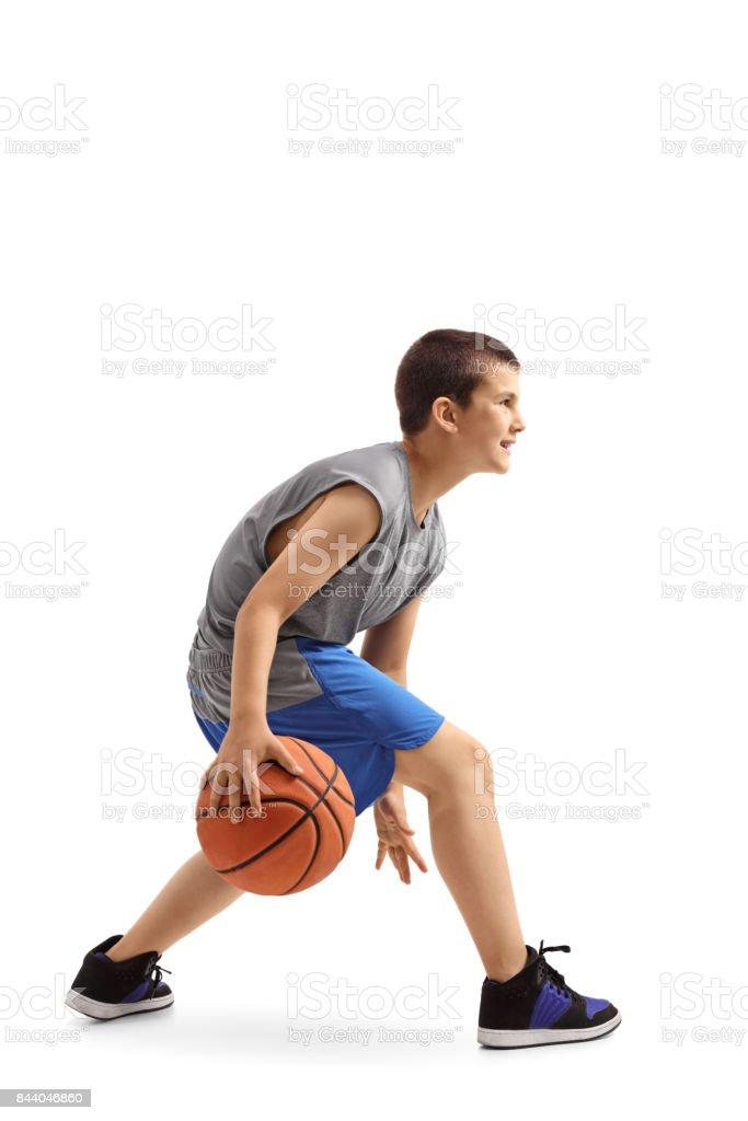 Profile shot of a boy dribbling a basketball stock photo