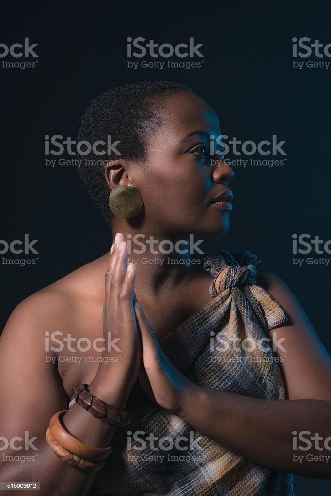 Profile shot of traditional xhosa woman wearing brown fabric. stock photo