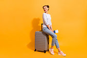 Profile side full length body size photo of cute charming youngster in light denim clothes standing in queue for her jet sitting on trolley bag holding documents on vivid background.