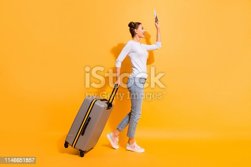istock Profile side full length body size photo of lady waiting for aircraft taxi hotel in airport holding documents baggage suitcase in hands in light pullover blue jeans isolated over vibrant background 1146651857