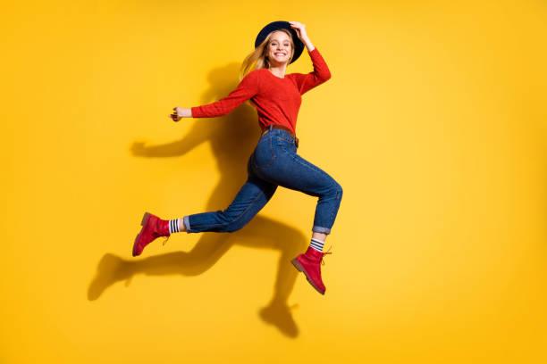 profil seite ganzlante körpergröße blick auf sie sie schön aussehende schöne schöne schöne schöne schöne, fröhliche sorglose mädchen mit spaß isoliert über hellen glanz orange orange hintergrund - damen jeans sale stock-fotos und bilder