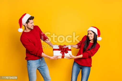 istock Profile side of angry couple pull package wear red sweater pullover santa claus cap denim jeans isolated over yellow background 1176734029