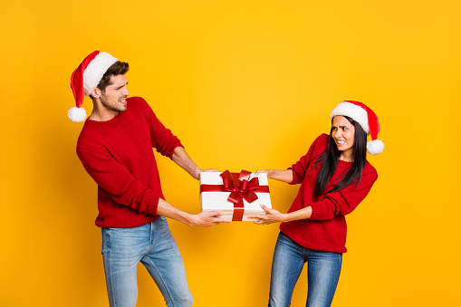 Profile side of angry couple pull package wear red sweater pullover santa claus cap denim jeans isolated over yellow background