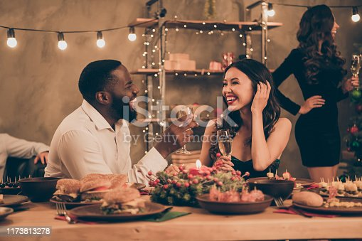 Profile side photo of cheerful couple of mixed-race man and chinese woman give toast hold champagne speak enjoy christmas, party x-mas night in house with table full of new year dinner feat indoors