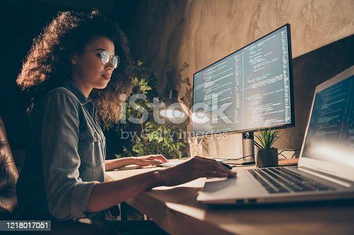 Profile side photo of concentrated skilled web expert afro american girl sit evening, desk use computer netbook work java script html back-end algorithm in workstation workplace