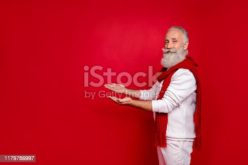 Profile side photo of cool elderly pensioner carrying copyspace wearing, white sweater pants trousers isolated over red background