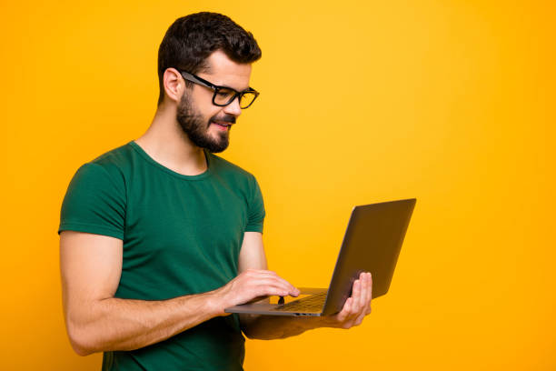 Profile side photo of positive cheerful guy use computer read study work information watch online start-up seminar wear good looking outfit isolated over yellow color background stock photo