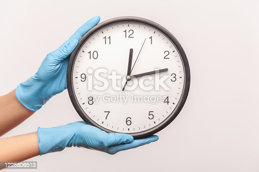 Profile side view closeup of human hand in blue surgical gloves holding analog clock. indoor, studio shot, isolated on gray background.