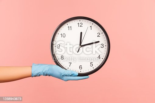 Profile side view closeup of human hand in blue surgical gloves holding analog clock. indoor, studio shot, isolated on pink background.