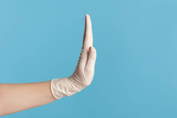 Profile side view closeup of human hand in white surgical gloves showing stop with hand. stock photo