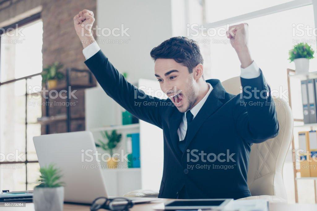 ハンサムなクレイジー感情的な楽しいハンサム叫んでのワークステーションの肘掛け椅子に座ってノート パソコンの前で手を上げる口を開けて生で叫んでプロファイル側ビュー縦半分になって ストックフォト