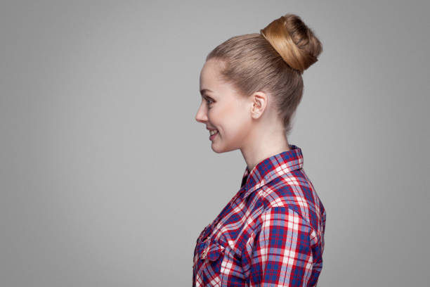 profile side view of beautiful blonde girl in red, pink checkered shirt, collected bun hairstyle standing and looking aside with toothy smile. profile side view of beautiful blonde girl in red, pink checkered shirt, collected bun hairstyle standing and looking aside with toothy smile. indoor studio shot. isolated on gray background profile view stock pictures, royalty-free photos & images