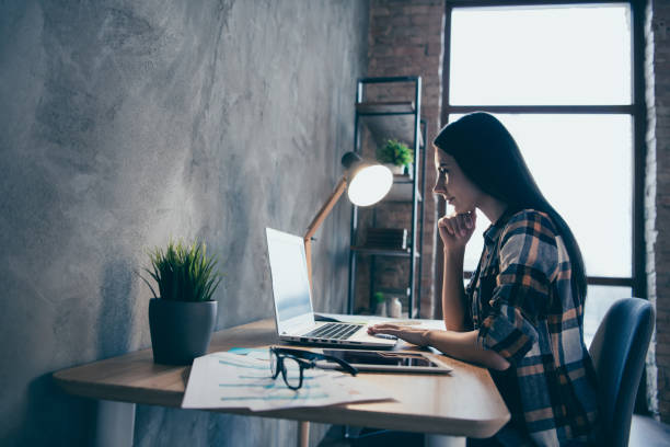 Profile side view of her she nice lovely charming attractive executive manager brunette lady checked shirt preparing marketing review report at industrial loft style interior room work place station Profile side view of her she nice lovely charming attractive executive manager brunette lady checked shirt preparing marketing review report at industrial loft style interior room work place station. desolation stock pictures, royalty-free photos & images