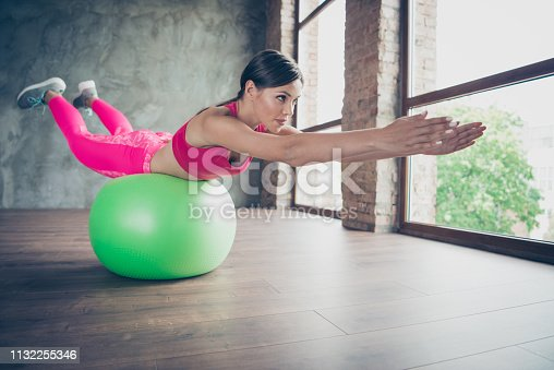 873786782istockphoto Profile side view of her she nice purposeful elastic graceful beautiful attractive lady wearing pink outfit lying on green fit-ball hands towards in modern loft industrial interior 1132255346