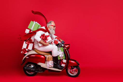 Profile side view of his he nice attractive trendy purposeful gray-haired man riding moto bike delivering pile stack purchase air wind blows isolated on bright vivid shine red background