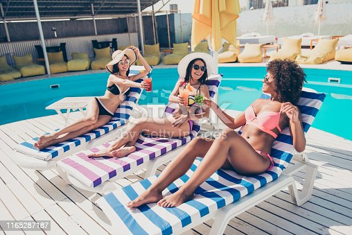 Profile side view of nice attractive glamorous cheerful cheery glad slim, thin fit slender girls lying on sunbed at luxurious spa resort hotel city club roof top talking clinking glasses