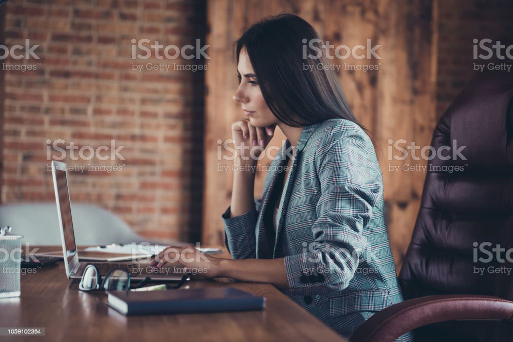 Profile side view of stylish lovely lady wearing grey jacket, typing business letter in laptop, sitting in modern loft work place work station - Royalty-free Adult Stock Photo