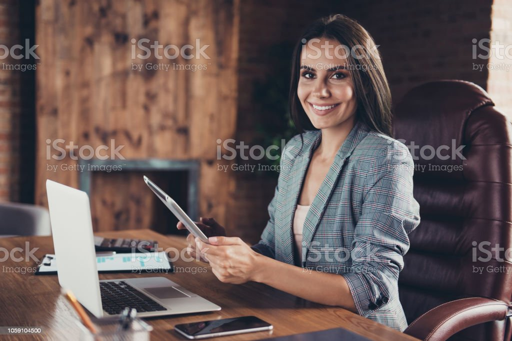 Profile side view photo of intelligent stylish boss in a gray checkered jacket sitting in office chair in workstation on industrial style half a turn with a tablet in hand stock photo