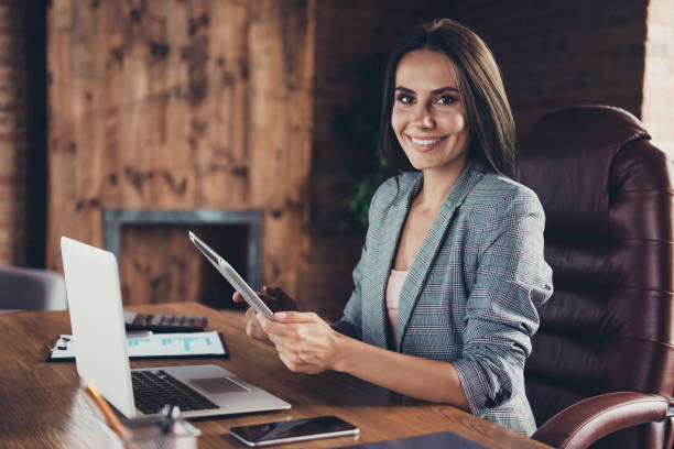 profile side view photo of intelligent stylish boss in a gray checkered jacket sitting in office chair in workstation on industrial style half a turn with a tablet in hand - business woman foto e immagini stock