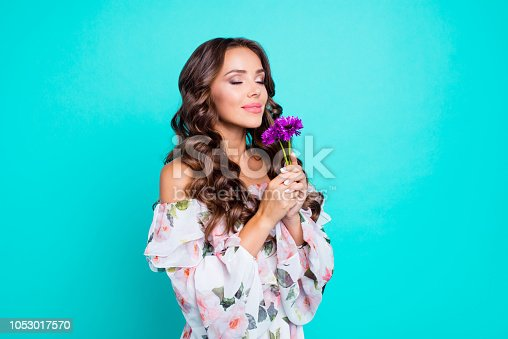 Profile side view photo of lovely, brunette young woman hold small bouquet of summer flowers in hand and breathe in their smell isolated on shine teal background stand half a turn