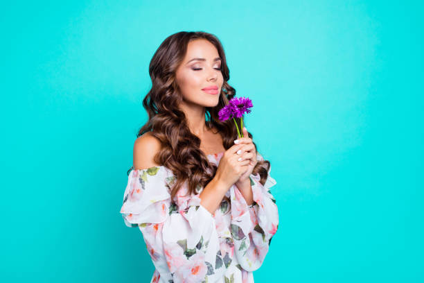 profile side view photo of lovely, brunette young woman hold small bouquet of summer flowers in hand and breathe in their smell isolated on shine teal background stand half a turn - annusare foto e immagini stock