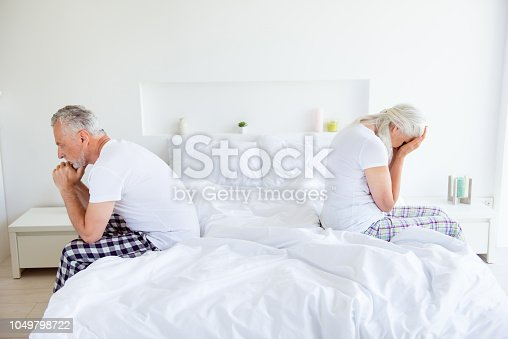 istock Profile side view photo of sad lovers after quarrel fight. Man and cry woman with gray hair sit back-to-back on the linen, sheets edge of the bed quarreled, did not talk 1049798722