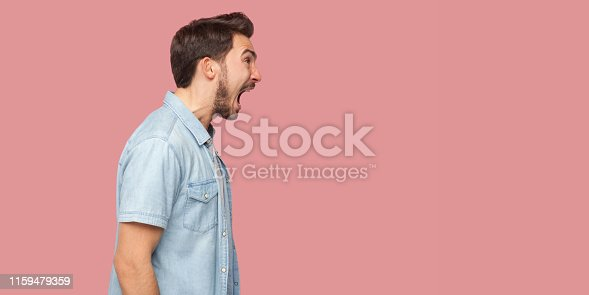 Profile side view portrait of angry or shocked handsome bearded young man in blue casual style shirt standing, looking forward and screaming. indoor studio shot, isolated on pink background.