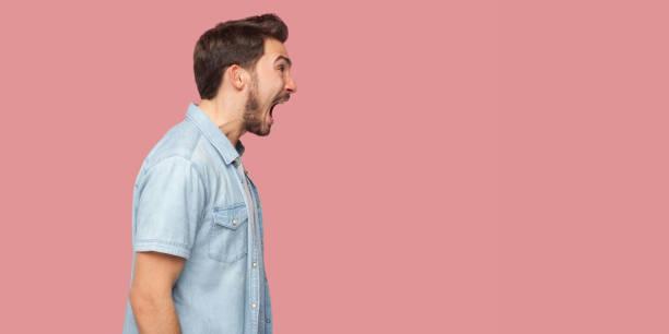 profiel zijaanzicht portret van boos of geschokt knappe baard jonge man in blauwe casual stijl shirt staande, kijken uit en schreeuwen. - roepen stockfoto's en -beelden