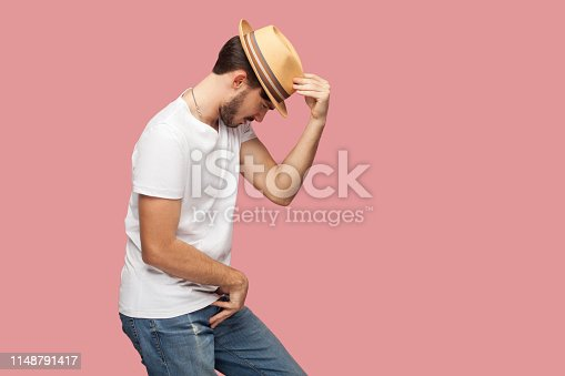 Profile side view portrait of bearded young dancer man in white shirt holding his hat and standing in michael jackson dancing pose. indoor studio shot, isolated on pink background copyspace.