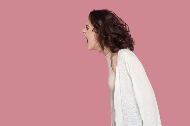 Profile side view portrait of brunette young woman with curly hairstyle in casual style standing and screaming. people expression and emotion. Profile side view portrait of brunette young woman with curly hairstyle in casual style standing and screaming. people expression and emotion. indoor studio shot isolated on pink background. anger stock pictures, royalty-free photos & images