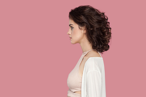 Profile side view portrait of calm beautiful brunette young woman with curly hairstyle in casual style standing with serious face and looking. indoor studio shot isolated on pink background.