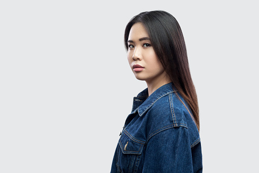 117149457 istock photo Profile side view portrait of calm serious beautiful brunette asian young woman in casual blue denim jacket with makeup standing and looking at camera 1134999358
