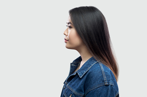 117149457 istock photo Profile side view portrait of calm serious beautiful brunette asian young woman in casual blue denim jacket with makeup standing and looking 1134999364