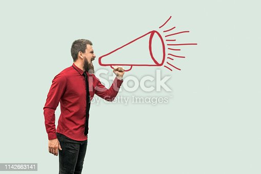 istock Profile side view portrait of handsome bearded man in red shirt standing and shouting on drawed megaphone 1142663141